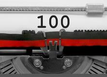 Nummer 100 vid den gamla skrivmaskinen på vitbok Arkivfoto