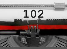 Nummer 102 vid den gamla skrivmaskinen på vitbok Arkivfoton