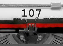 Nummer 107 vid den gamla skrivmaskinen på vitbok Arkivfoton