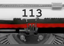 Nummer 113 vid den gamla skrivmaskinen på vitbok Arkivfoton