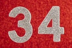 Nummer vierendertig zilveren kleur over een rode achtergrond Anniversa Stock Afbeeldingen