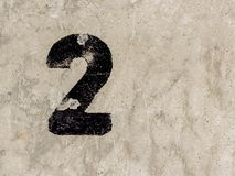 Nummer zwei 2 auf Betonmauerhintergrund Stockbild
