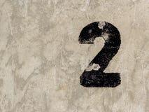 Nummer zwei 2 auf Betonmauerhintergrund Stockfotografie