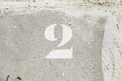 Nummer zwei durch eine Backsteinmauer Stockfoto