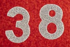Nummerieren Sie achtunddreißig silberne Farbe über einem roten Hintergrund Annivers Stockfoto