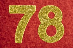 Nummerieren Sie achtundsiebzig goldene Farbe über einem roten Hintergrund Anniver Stockbilder