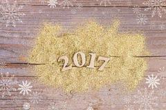 Nummerieren Sie 2017 auf hölzernem Hintergrund mit goldenem Funkeln Lizenzfreies Stockfoto