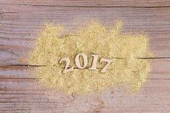 Nummerieren Sie 2017 auf hölzernem Hintergrund mit goldenem Funkeln Stockbilder