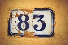 Nummerieren Sie dreiundachzig Emailtürzahl auf Gipswand Stockfoto