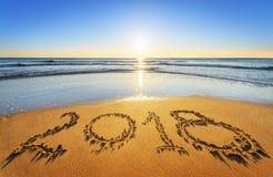 Nummerieren Sie 2018 geschrieben auf Küstensand bei Sonnenaufgang Konzept von upco Stockfoto