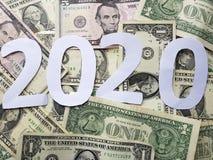 nummerieren Sie 2020 im Weiß mit Hintergrund von Dollarscheinen Lizenzfreies Stockbild