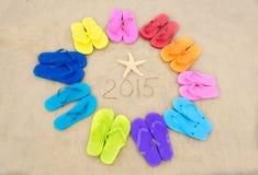 Nummerieren Sie 2015 mit Farbflipflops auf dem Strand Stockbild