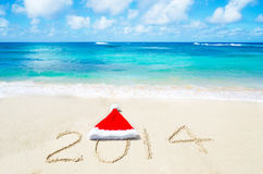 Nummerieren Sie 2014 mit Weihnachtshut auf dem sandigen Strand Stockfoto