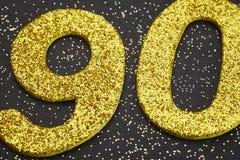 Nummerieren Sie neunzig goldene Farbe über einem schwarzen Hintergrund jahrestag Stockfoto