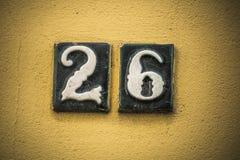 Nummerieren Sie sechsundzwanzig in angehobenen Zahlen auf Gipswand Stockfoto