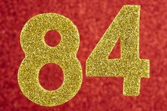 Nummerieren Sie vierundachzig gelbe Farbe über einem roten Hintergrund Anniversa Lizenzfreie Stockfotos
