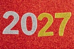 Nummerieren Sie zwei tausend und siebenundzwanzig über einem roten Hintergrund anni Lizenzfreies Stockfoto