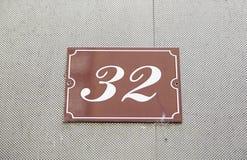 Nummerieren Sie zweiunddreißig auf der Wand eines Hauses Stockfotos