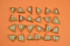 24 nummerierte Einführungsplätzchen auf Orange Lizenzfreie Stockfotos