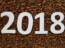 numrera 2018 i vit med grillade kaffebönor bakgrund, designen för nytt år royaltyfri fotografi