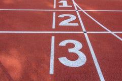 Numrera 1 2 och 3 av loppspåret Arkivfoto