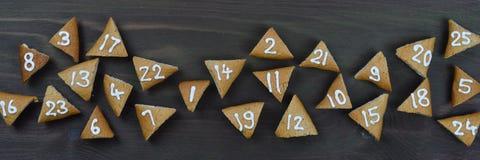 25 numrerade adventkakor på brunt trä Arkivbilder