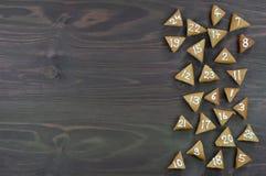 25 numrerade adventkakor på brunt trä Royaltyfria Bilder