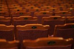 Numrerade teaterstolar med röd sammet Royaltyfri Foto
