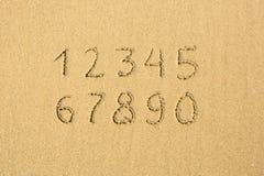 Numrerar skriftligt på en sandig strand Arkivfoton