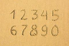 Numrerar skriftligt på en sandig strand Utbildning Arkivbilder