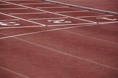 Numrerar vägvisaren i ett idrotts- rinnande spår Arkivfoto