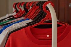 Numret av mång--färgade T-tröja och omslag väger på hängare arkivfoto