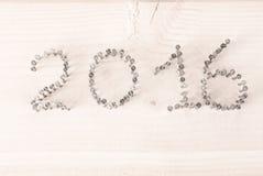 Numret 2016 av spikar på en ljus träbakgrund Jul Fotografering för Bildbyråer