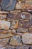 Numret 48 i vit målarfärg på en gammal stenhusvägg i byn av Banya, Bulgarien Royaltyfri Bild