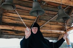 Nun bell-ringer in orthodox church. Starosillia, Volyn / Ukraine - February 04 2009: Woman bell-ringer in orthodox church bell tower Stock Photography