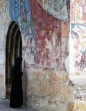 A nun in black habit standing in front of a colorful Orthodox temple in northern Romania stock image