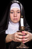 Nun with a burning candle Stock Photo