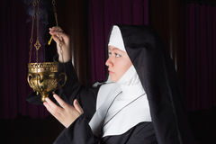 Nun burning incense. Nun in habit lighting a copper incense burner in church royalty free stock images