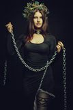 Nun with chains. Seductive nun posing with chains over dark background royalty free stock photo