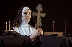 Nun with cross. Young catholic nun is praying. Orthodox cross in her hands. Photo on black background Royalty Free Stock Photography