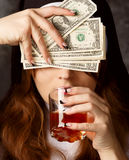 Nun holding dollar bills and glass with alcohol on dark background.woman hand with cuts closed eyes and drank alcohol Stock Photo