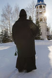 Nun holds a rosary in hands near bell tower in orthodox monastery, Russia. Vertical Stock Photography