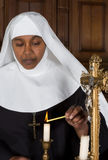 Nun lighting a candle. Mature nun lighting a candle on the altar of a medieval church stock photos