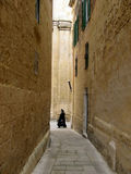 Nun and old walls. Black robed nun walking through a side-streets in the medieval city of Medina, Malta Stock Photography