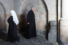 Nun passing priest Stock Photo