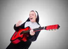 Nun playing guitar against the gradient Royalty Free Stock Image