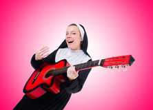 Nun playing guitar against the gradient Stock Images