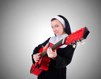 Nun playing guitar against the gradient Stock Image