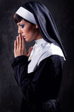 Nun praying. Young attractive nun praying indoors Stock Photo