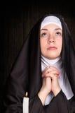 Nun praying and burning candle Royalty Free Stock Photo